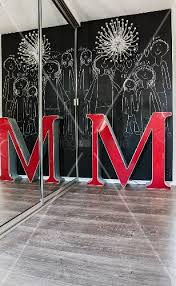 large decorative letter in front of children s drawings on chalkboard wall with wall mounted designer lamp