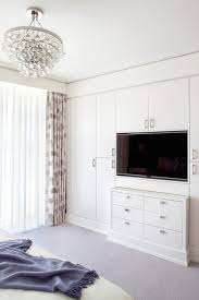 stunning bedroom with wall of built in closets framing built in flatscreen tv over built in dresser across from bed illuminated by robert abbey bling