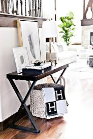 basket dd with a black and gray hermes avalon blanket tucked under a dark stained x based console table topped with coffee table book and art