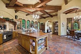 Open Concept Kitchen With High Ceilings Arched Doorways And Spanish Tile  Flooring