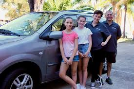 two pas and their daughters outside a car