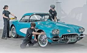 detailers from left aaron vanausdall reece peterat bennett work on a 1960 chevrolet corvette at dellenbach motors in fort collins colo
