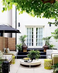 moroccan patio furniture. black steps lead to a contemporary patio filled with white wicker sofa and chairs adorned gray trellis pillows as well yellow stool tables facing moroccan furniture r