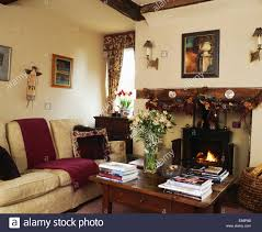 dried flower garland on beam above wood burning stove in cottage living room with s on wooden chest