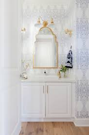 Elegant printed wallpaper in blue and white with gold accents and mirror  above the sink with
