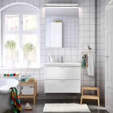scandinavian bathroom design featuring floating white wooden vanity cabinets under frameless wall mirror and white rectangle small bath mat