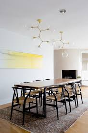 earthy furniture. earthy modern dining room with gold light fixture black wishbone chairs live edge furniture