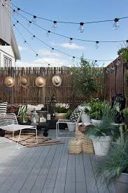 cute little outdoor setup sun hats hung on the fence make a thoughtful addition for daytime users while lovely string lights provide atmosphere in the