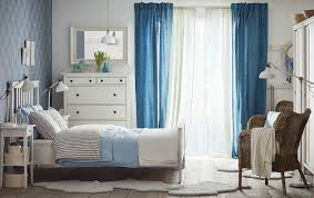 A medium sized bedroom with a white bed for two with bedlinen in light blue  and