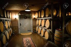 stacked oak wine barrels. The Dimly Lit Room Elegantly Shines Upon Stacked Oak Wine Barrels Stock Photo - N