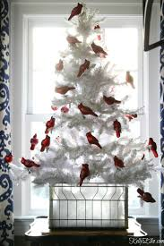 Love this flocked white Christmas tree with a flock of red cardinal  ornaments kellyelko.com