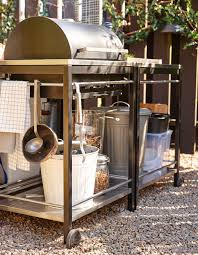 A grill with space for storing charcoal or a gas bottle underneath, as well  as
