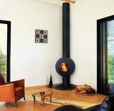 unique and small modern wood burning stove in black some wood logs an arm  chair with