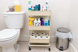 the ikea raskog cart holding bathroom supplies between a toilet and trash can