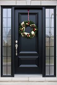 here s a truly bespoke black door with silver hardware flanked by a pair of smoked gl windows