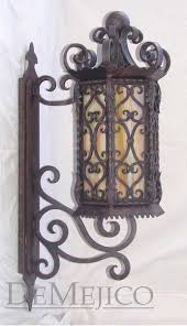 the santa barbara wall mount is a hand forged spanish wall mount spanish scrollwork with a small twisted rope design surrounds a single imitation candle
