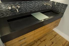 bathroom rectangle black glossy concrete sink over brown wooden vanity plus steel faucet on black