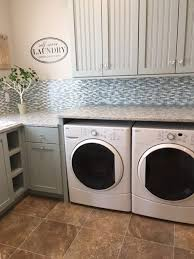 laundry room with solid surface countertop mixed tile backsplash luxury vinyl tile flooring