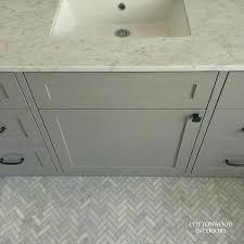 herringbone marble floor herringbone marble tile floor bathroom traditional with double sinks wall lighting freestanding bathtub