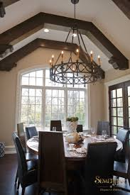 the wrought iron chandelier and rich dark mahogany doors complement the beams and add to the old world appeal
