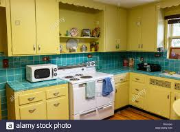 Retro 1940s Style Kitchen With Yellow Cabinets And Blue Tile At The
