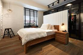a high headboard separates the one wall wardrobe from the bed creating a walk in closet as a result