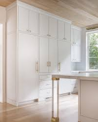 brass and lucite legs placed on gray wash wood floors under an oak plank ceiling accent a white island topped with a gray and white marble countertop