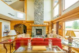 a modernized log cabin with an enormous stone fireplace the wooden mantle is wider than
