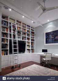 office built in. Built-in Shelving In Home Office With Mobile Ladder And Gregory Crewdson Print On The Wall. New York, USA. Built N