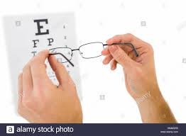 Glasses Held Up To Read Eye Test On White Background Stock