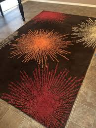 large brown area rug with splashes of red orange and taupe the colored splashes are raised pieces that pop up a bit