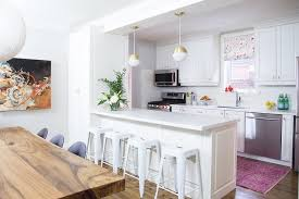 white and pink kitchen design with gold pendant lights