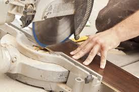 contractor using circular saw cutting of new laminate flooring renovation