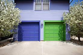 a periwinkle two story house has two garage doors one painted lime green