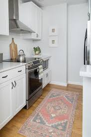 white kitchen with pink and black rug