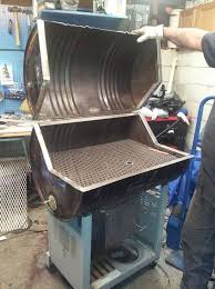 homemade charcoal grill and smoker constructed from a steel drum angle iron wire mesh and a wheeled stand