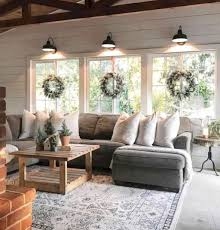 wood ceiling planks grey microfiber u shape sectional sofa with white pillows snow persian area rug wooden coffee table black allenby drake wall sconce