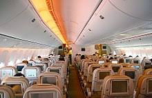 Airliner cabin. Rows of seats arranged between two aisles. Each seatback  has a monitor