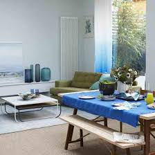 green and blue living room. open-plan living room with white walls, neutral floor, wood table, blue green and