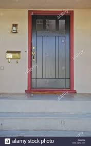 black door with br ing with burgundy trim on a beige stucco house stock image