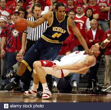 Wisconsin center Jason Chappell goes down to the floor as Michigan center Courtney  Sims (44) commits an offensive foul as he drives the baseline during their  NCAA Basketball Big Ten Conference game