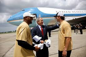 president george w bush is welcomed by new orleans saints running running back deuce mcallister left and saints quarterback drew brees upon his arrival wednesday aug 20 2008 to the louis armstrong international