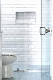 subway tile shower niche behind a seamless glass walk in shower enclosure white beveled surround tiles