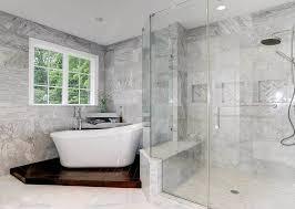 master bathroom with marble tile shower rainshower head and freestanding tub on pedestal