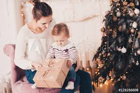 Smiling young mother open Christmas presents with baby girl 1 year old under tree. Holiday season.