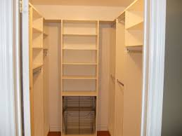 small walk in closet in white theme featured wall shelves and two tiers wire baskets