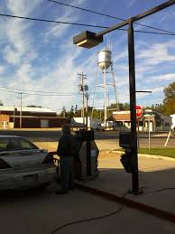 nick s photo essay small town life  jim owner and mechanic at dexter mobil fills a customer s car above him rises the town s water tower