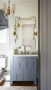 gray washstand with greek key mirror and brass and glass chandelier