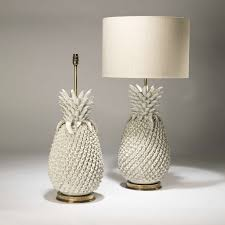 pair of large cream ceramic pineapple lamps on distressed brass bases e6