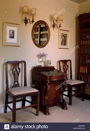 Dining chairs on either side of small antique desk in old